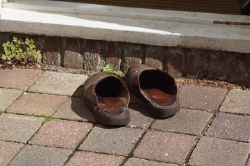 Old, brown, worn slippers on the stone tiles of the back entrance of a house. Summer, Netherlands,
