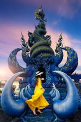 Wall Mural - Woman wearing yellow dress at Wat rong suea ten or blue temple in Chiang rai, Thailand.