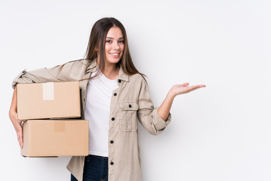 Young caucasian woman moving to a new home showing a copy space on a palm and holding another hand on waist.
