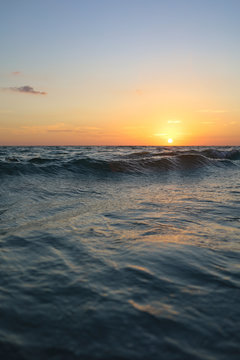 Wading into Sunset in Sarasota Lido Key, Florida. Crisp waves in dark waters with clear sky sunset. Sun sets over crashing waves of Gulf of Mexico near Siesta Key.