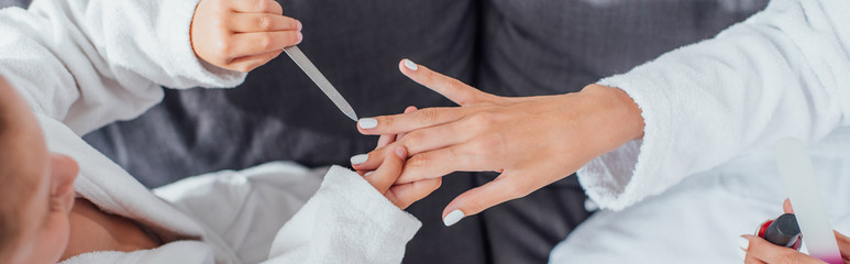 cropped view of girl with nail file making manicure to mother, horizontal image