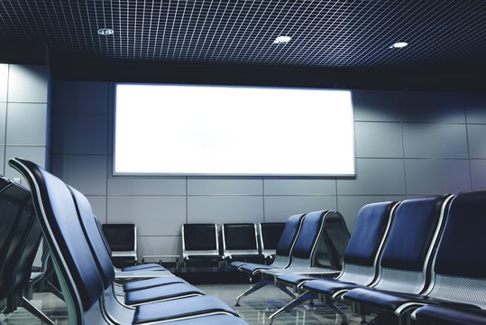 Blank billboard with clean space for publicity content or text message, advertising mock up in interior, public commercial board in waiting of airport hall with empty chairs, template banner indoors
