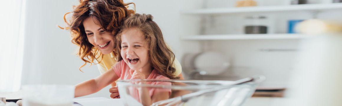 selective focus of excited mother and daughter laughing while cooking in kitchen, website header