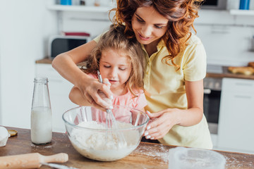 selective focus of mom kneading dough in glass bow near daughter and bottle of milk
