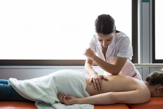 Hands of female physiotherapist massaging the back of a woman