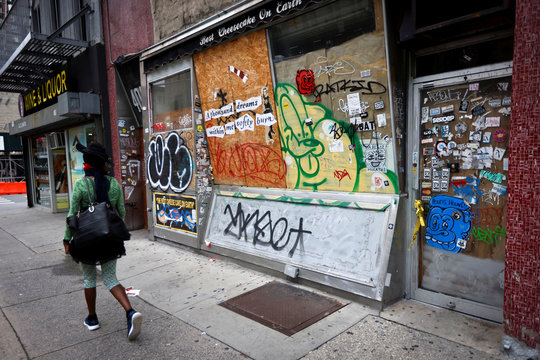 A woman walks past closed business on 8th Avenue in New York