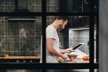 Mature man standing in kitchen, preparing food, using online recipe