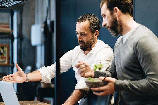 Mature friends working on laptop in kitchen, one eating salad