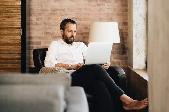 Mature man sitting in armchair, using laptop