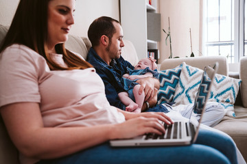 Father carrying sleeping daughter while mother using laptop on sofa