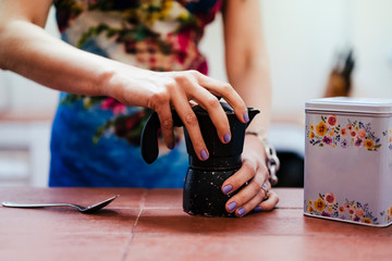 Close-up of woman's hands using coffee pot in kitchen