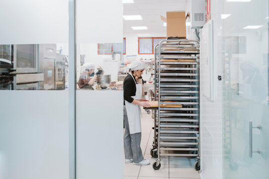 Male and female bakers working at bakery