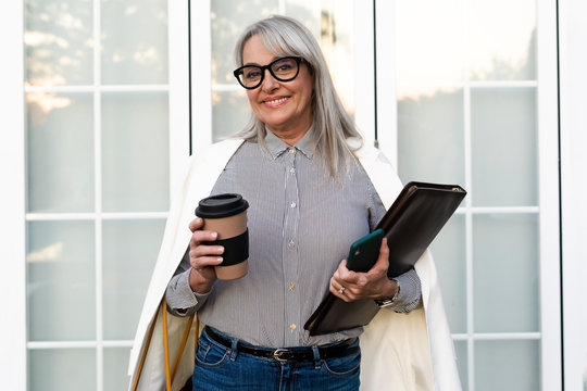 Smiling senior businesswoman holding disposable cup with file and smart phone against office door