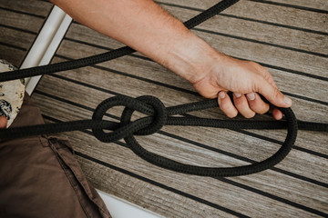 Cropped hands of sailor tying marine knot in sailboat