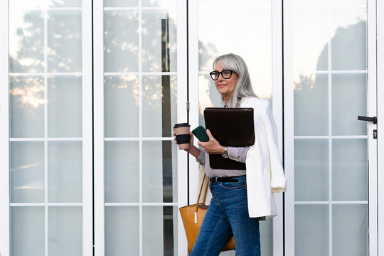 Female entrepreneur looking away while holding disposable cup and file against door