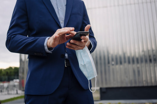 Businessman with protective face mask using smartphone in the city