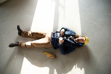 Male architect sleeping on floor in renovating house