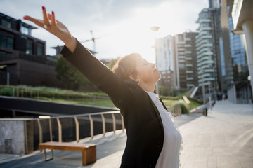 Businesswoman with arms raised standing on footpath in city