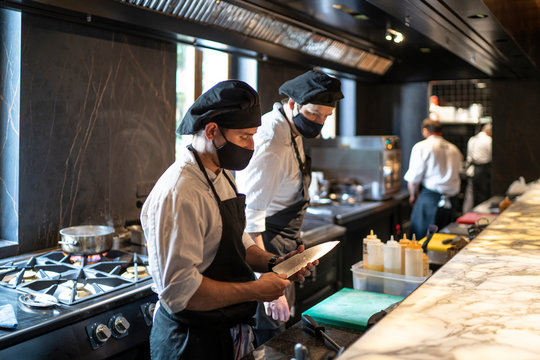 Chefs wearing protective face masks working together in restaurant kitchen