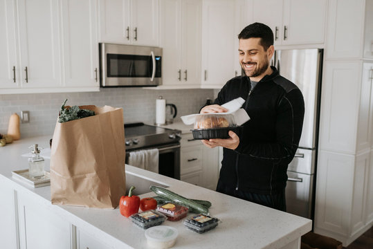 Smiling mid adult man cleaning groceries in kitchen at home