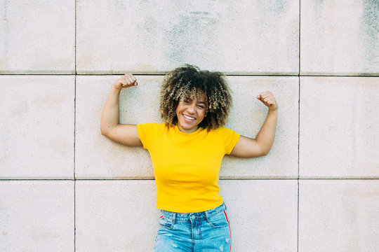 Portrait of smiling strong woman on wall
