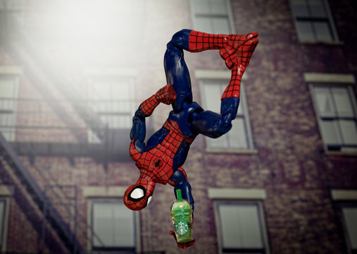 NEW YORK USA, AUGUST 19 2020: superhero Spiderman hanging upside down from a web with a Starbucks Frappuccino - Hasbro Legends action figure