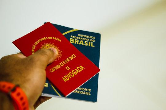 Hand holds identification document of lawyer from Brazil. Carteira da OAB (Ordem dos Advogados do Brasil) e o New Passporte of the República Federativa do Brasil - Mercosur Passport