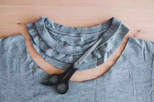 upcycling old clothes concept, t-shirt with scissors to cut a new neckline