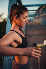 Young sporty woman relaxing and listening music after workout on sunset