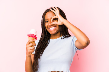 Young african american woman holding an ice cream isolated excited keeping ok gesture on eye.