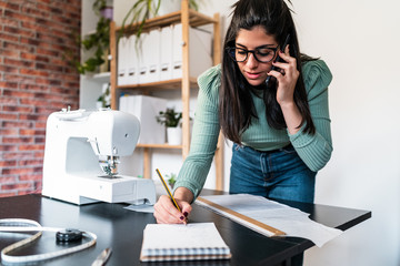 Young ethnic seamstress in eyeglasses taking notes standing leaned forward while using straightedge at table with papers and scissors in loft style studio