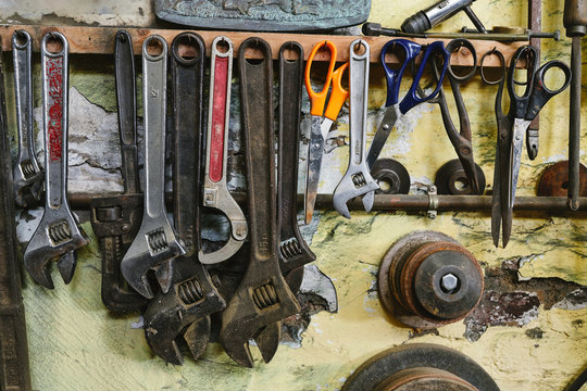 Set of different tools with various wrench and scissors on concrete wall in studio