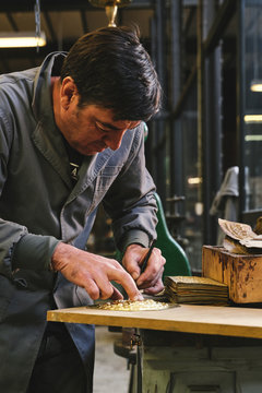 Concentrated middle aged ethnic goldsmith in uniform working with gold on wooden table using metal stick while leaning forward in studio