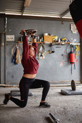 Side view full body strong sportswoman in sportswear performing lunges and lifting heavy barbell plate above head while working out in garage gym