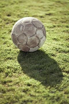 From above of used leather football ball with hexagon pattern and shabby surface on green lawn covered with artificial turf roll