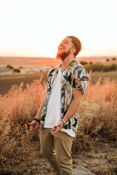 Cheerful slim bearded male in wristwatch and casual wear standing with thumbs up near growing grass illuminated by sun at sundown in summer in countryside and looking up
