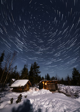 Cozy small wooden houses in snowy terrain surrounded by coniferous forest against picturesque starry night sky