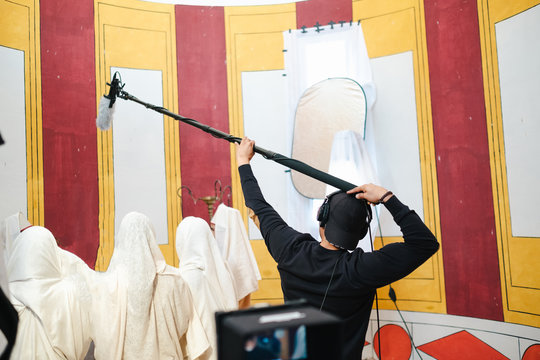 Back view faceless assistant raising professional shotgun microphone above group of Arabs in white national clothes while working in creative studio during video recording