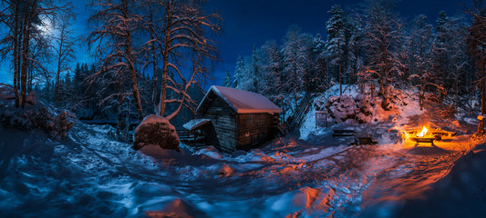 Small wooden house located in picturesque winter forest covered by snow near bonfire at night