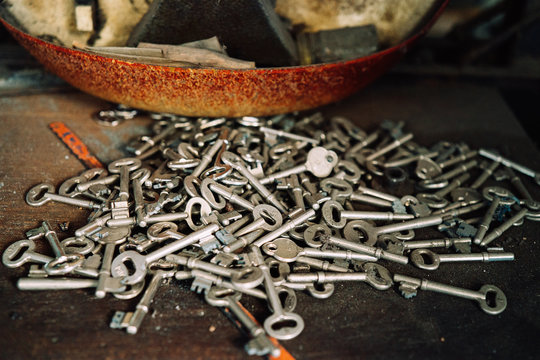 Heap of various metal keys placed on weathered table in old workshop
