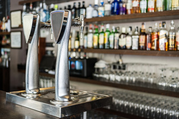 Metallic beer column placed on bar counter against shelves with alcoholic drinks in glass bottles