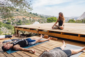 Female yoga trainer sitting in Lotus pose instructing students relaxing in Corpse asana after finishing outdoor workout on sunny day