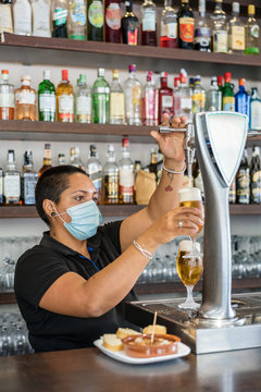 Ethnic woman pouring beer into glass from beer column while working as barkeeper in modern bar