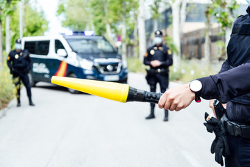 Crop anonymous police officer prohibiting car driving on street with yellow traffic baton during coronavirus on sunny day