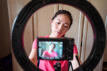 Focused young Asian woman stetting camera on tripod with ring light while preparing for creating new beauty blog at home