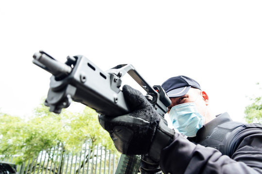 From below of serious spec ops police officer in  protective uniform and medical mask aiming submachine gun during police operation