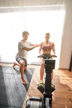 Full body of woman exercising on rowing machine with personal trainer in modern gym at daytime