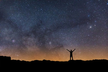 Man observing the night sky with the Milky Way in the background while you have open arms