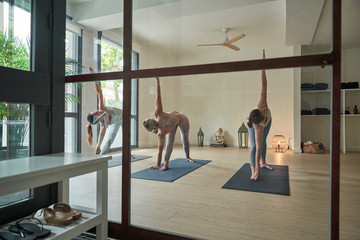 Full body of young sportswomen in active wear practicing yoga and performing extended side angle pose stretching asanas in spacious studio in morning