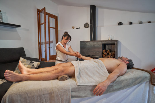 Female therapist standing near massage table and stretching arm of male patient
